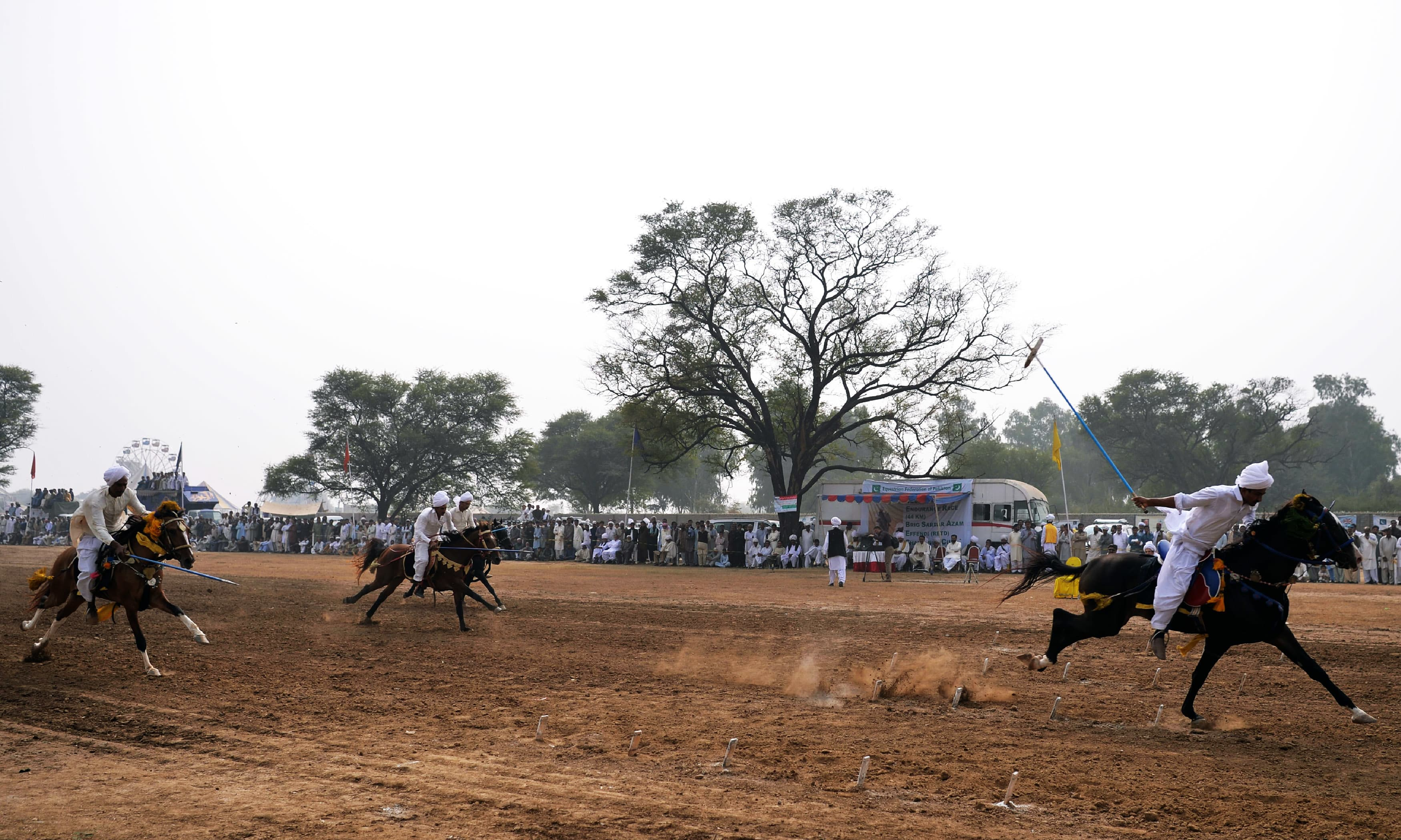 Riders charge across a course holding a lance to pick up pegs at a tent-pegging competition. —AFP