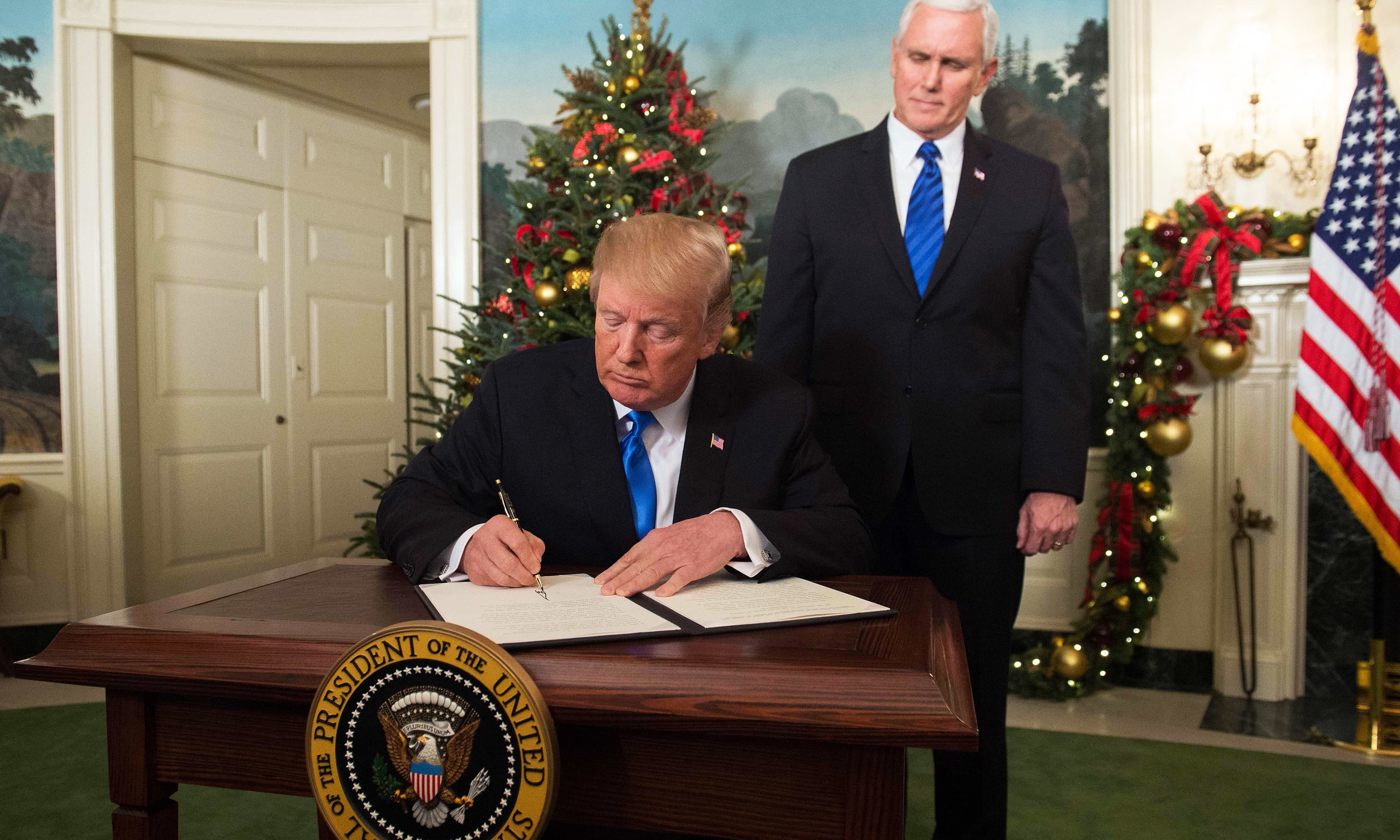 Trump signs a memorandum after he delivered a statement on Jerusalem. —AFP