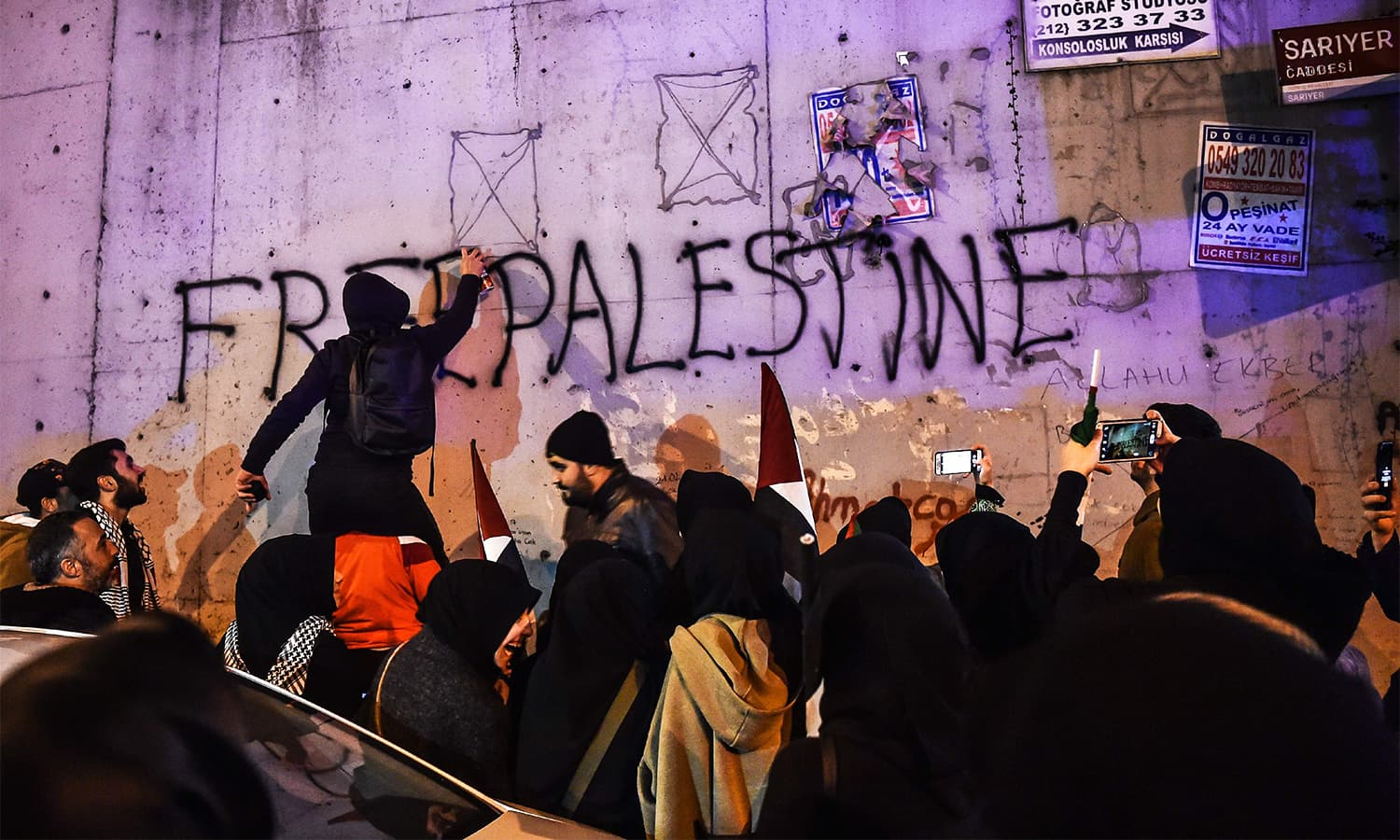 "A protester spray-paints ""Free Palaestine"" on a wall during a demonstration in front of the US consulate in Istanbul.— AFP"