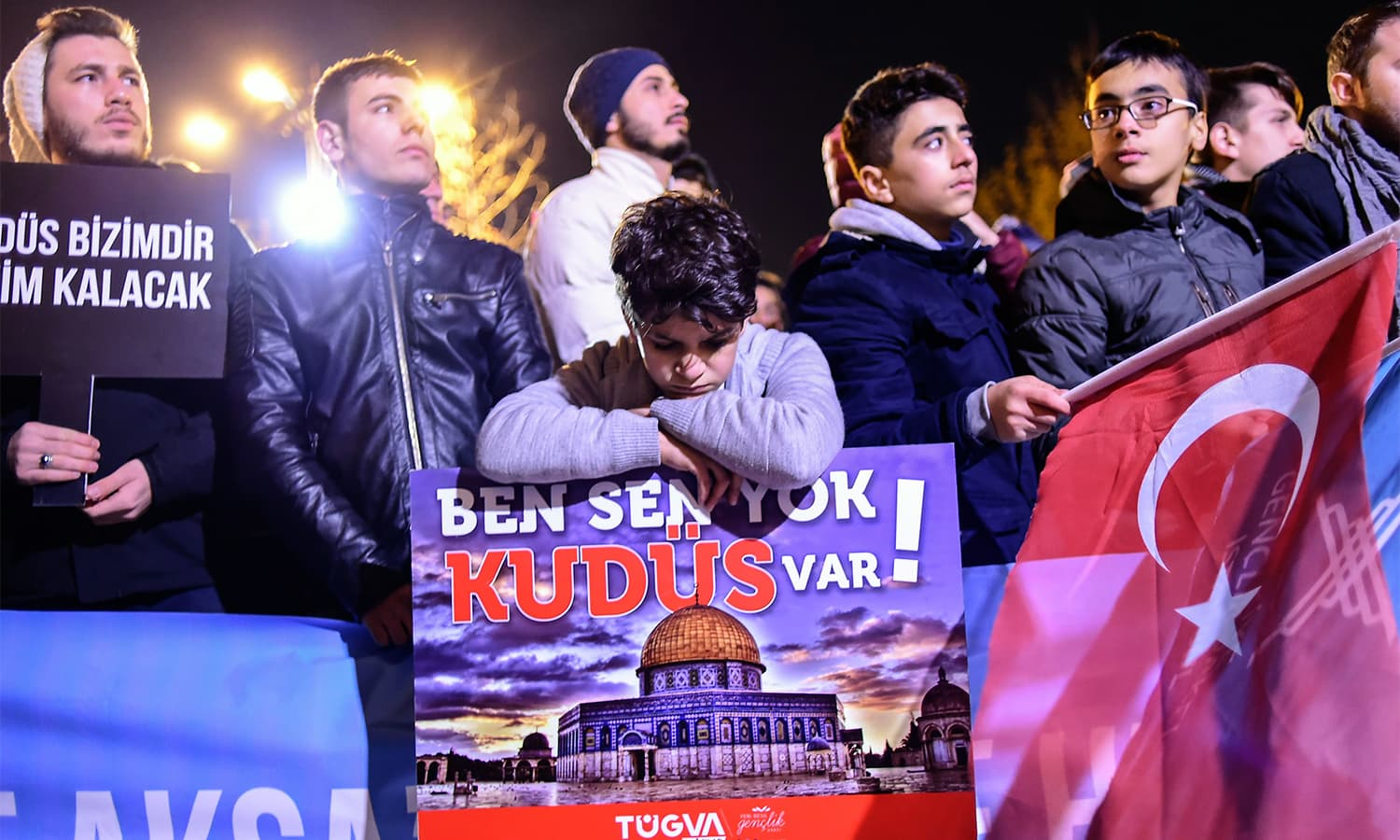 "A young boy leans on a sign (C) reading ""There is no you or me, there is Jerusalem"" during a demonstration at Fatih Mosque in Istanbul.— AFP"
