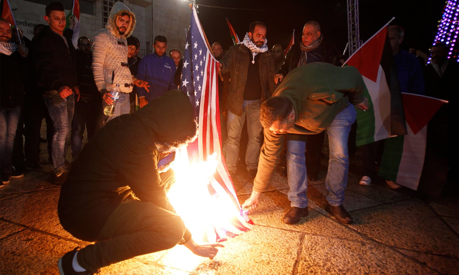 Palestinian demonstrators burn the US flag in Bethlehem's Manger Square in protest.— AFP