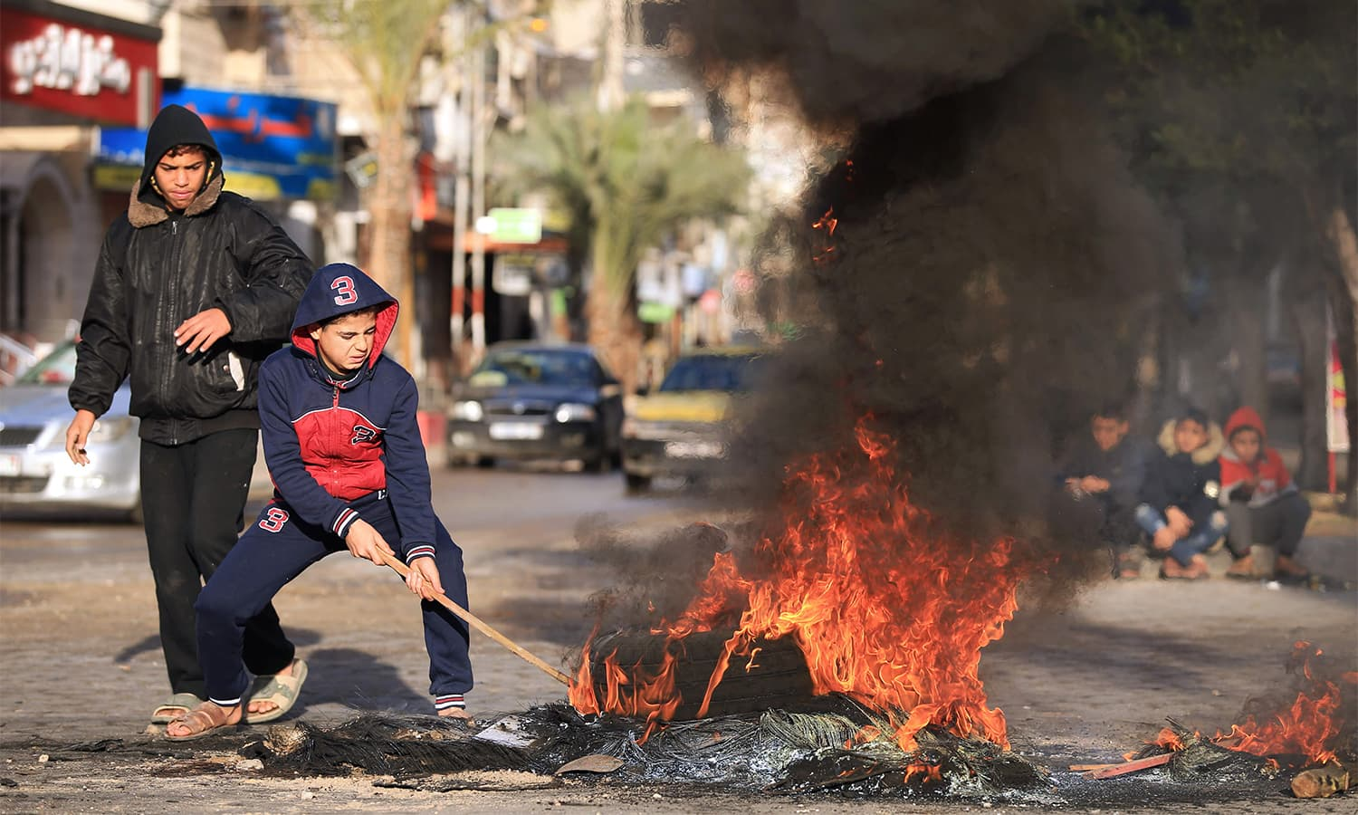 Palestinian youths set tires ablaze during a protest against Trump's decision to recognise Jerusalem as the capital of Israel, in Gaza City, on Thursday.— AFP