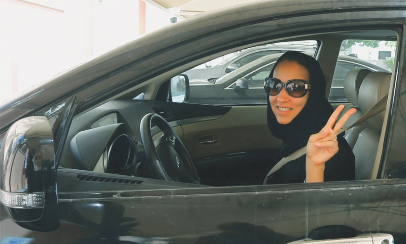 Manal al-Sharif flashes the victory sign from behind the wheel of her car | AFP