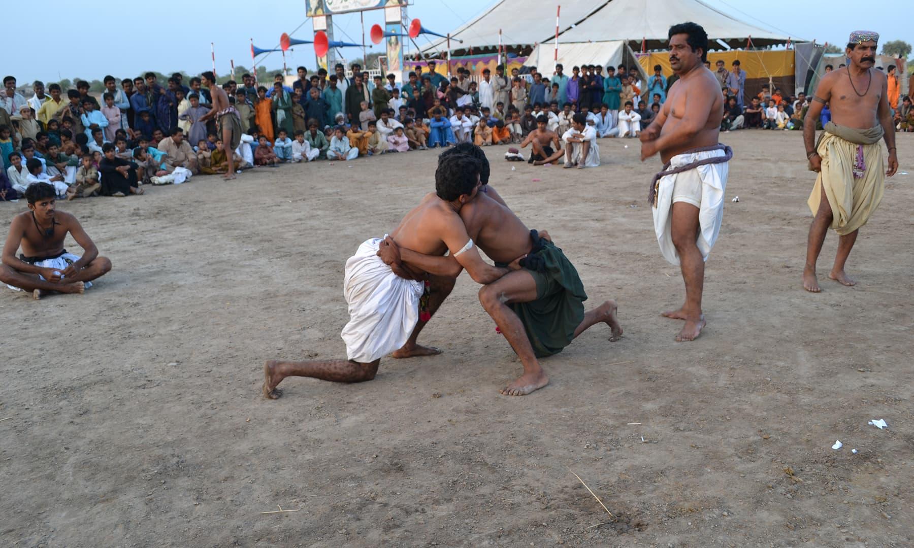 ملاکھڑے میں دو پہلوان مختلف داؤ آزماتے ہوئے ایک دوسرے کو پچھاڑنے کی کوشش کرتے ہیں—تصویر ابوبکر شیخ