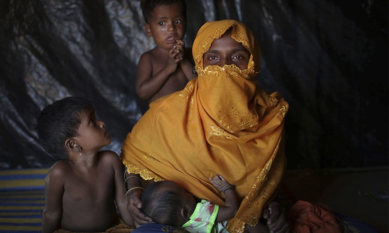 K, 25, is photographed as she nurses her baby with her two children beside her in their tent in Kutupalong refugee camp in Bangladesh. ─ AP