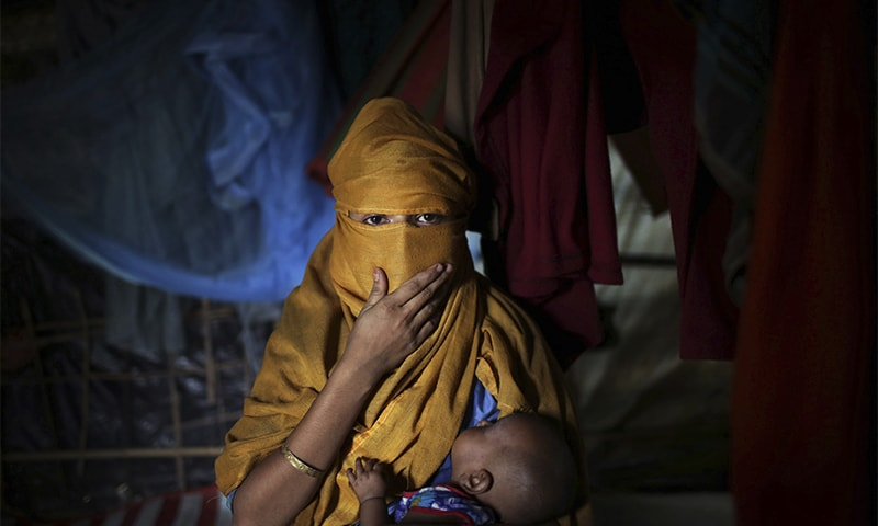 S, 16, carries her baby while being photographed in her tent in Kutupalong refugee camp in Bangladesh. ─ AP