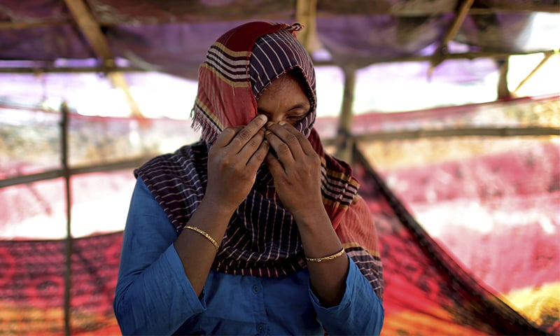 D, 30, hides her face while she was being photographed in a friend's tent in Kutupalong refugee camp in Bangladesh. ─ AP