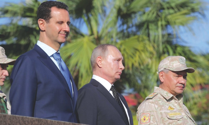 LATAKIA (Syria): Russian President Vladimir Putin (C), Defence Minister Sergei Shoigu (R) and Syrian President Bashar al-Assad visit the Hmeymim air base on Monday.—Reuters