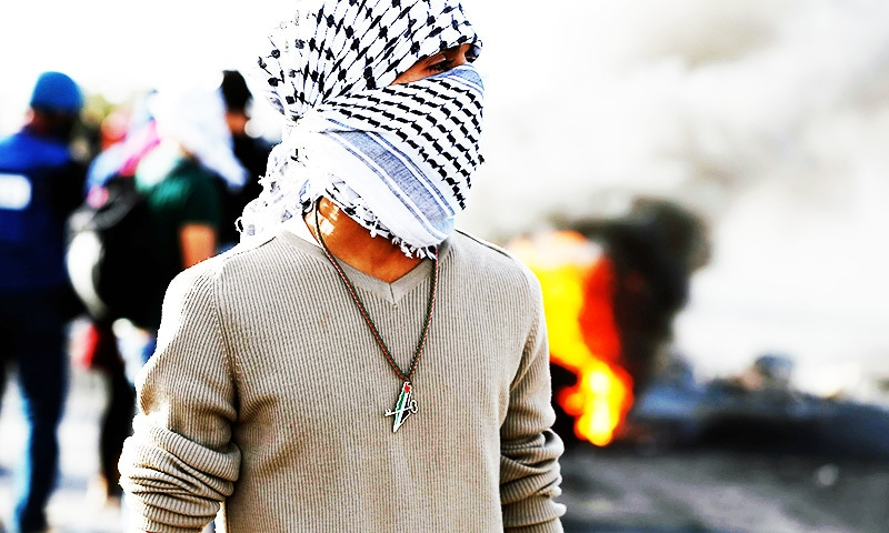 A masked Palestinian protester, wearing a necklace showing a map of mandatory Palestine coloured with the Palestinian flag and with a crossed key above, stands amidst smoke from flaimg tires and tear gas fumes during clashes with Israeli forces in  West Bank.—AFP