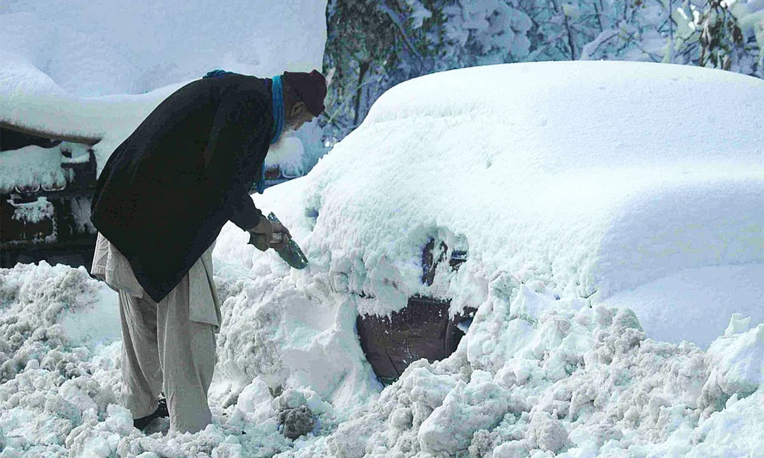 A man removes snow from a car during the first snowfall of the year in Murree.— APP