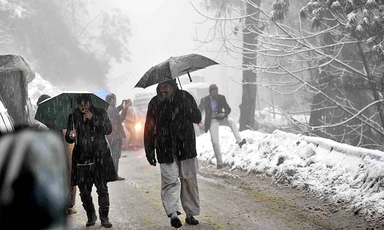 People walk under umbrellas during the first snowfall of the year in Murree.— APP