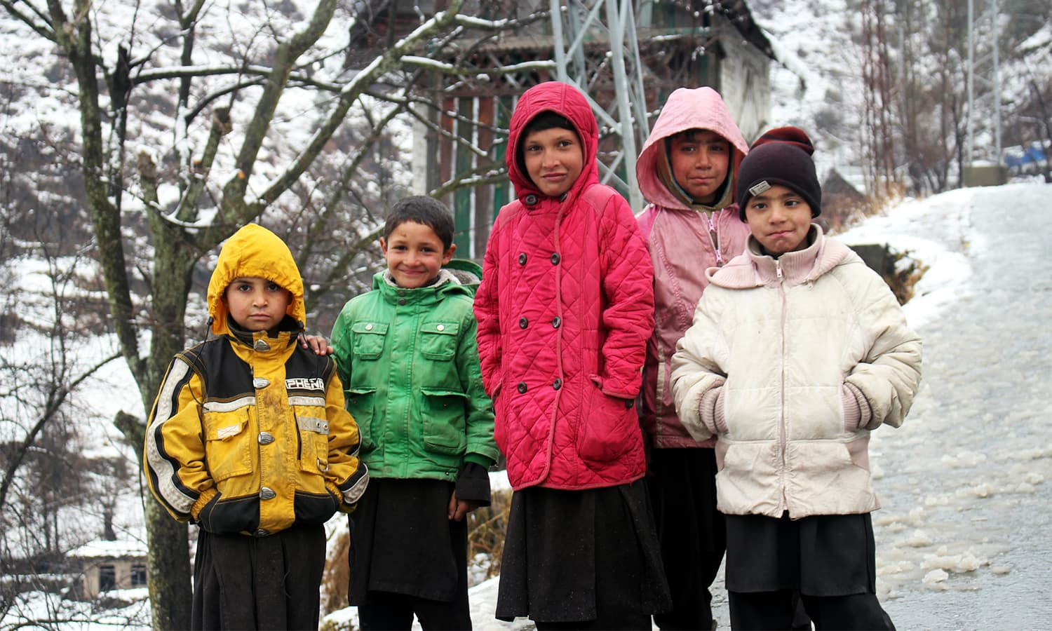 Children enjoying snow pose for a photo in Shangla.— Umar Bacha