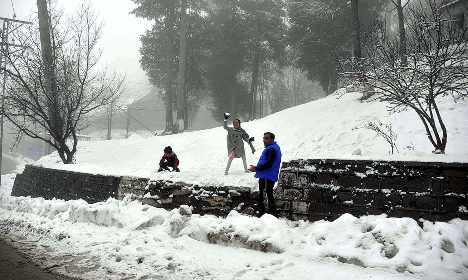 Children play with snow during the first snowfall of the year in the hill resort of Murree.— APP