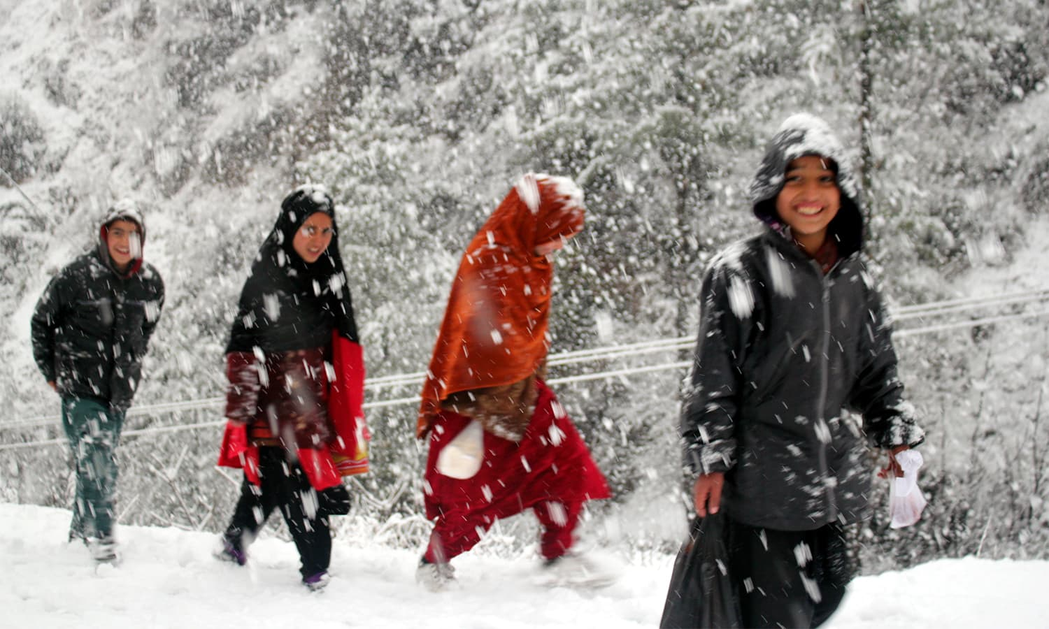 Children walk on a snow-covered hill in Shangla.— Umar Bacha
