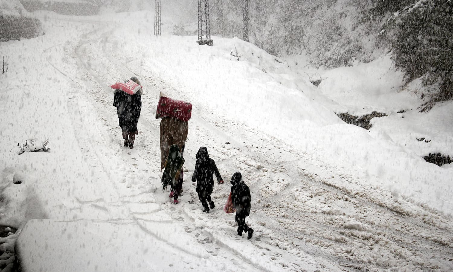 People walk on a snow-covered road in Shangla.— Umar Bacha