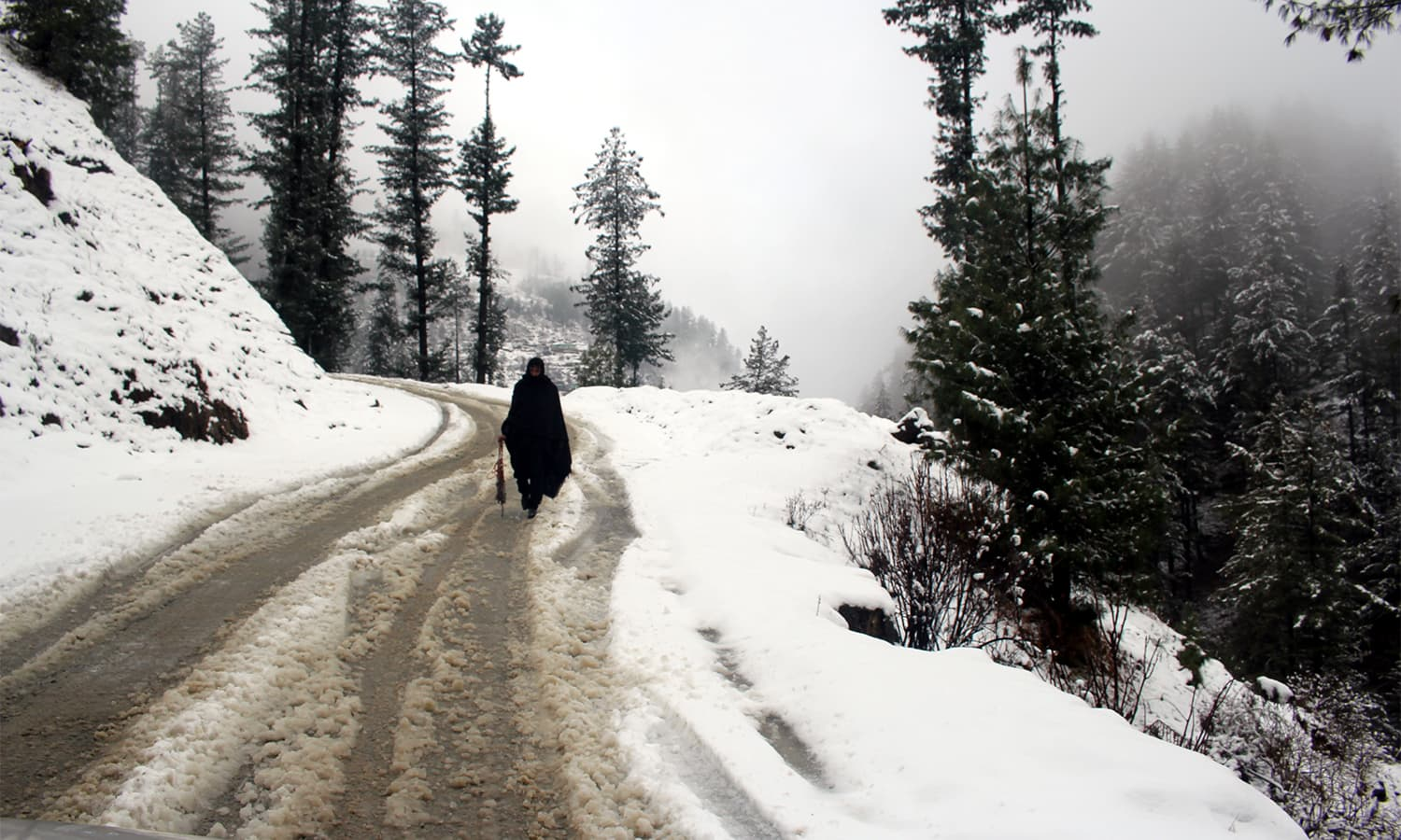 A man walks on a road covered with snow in Shangla.— Umar Bacha