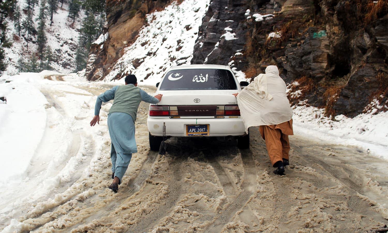Two men push a car through snow in Shangla.— Umar Bacha