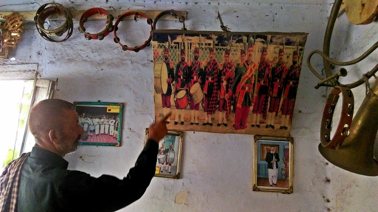 Shokat Ali showing old family pictures.