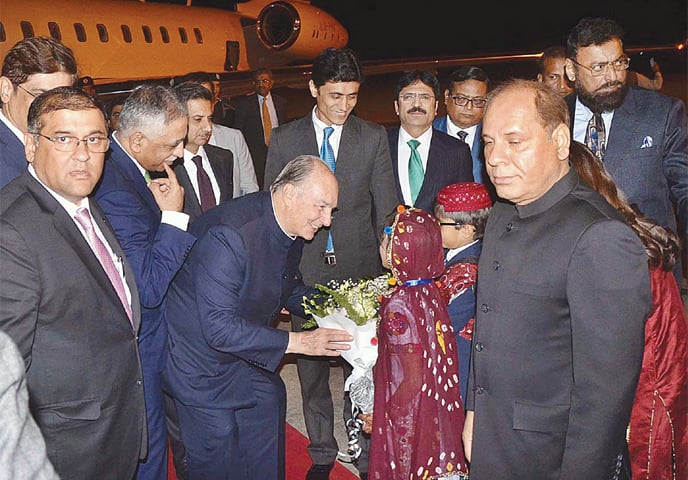 KARACHI: Two children present a bouquet to Prince Karim Aga Khan at the airport on Thursday. Sindh Governor Muhammad Zubair was at Quaid-i-Azam International Airport to welcome the spiritual leader of the Ismaili community.—APP