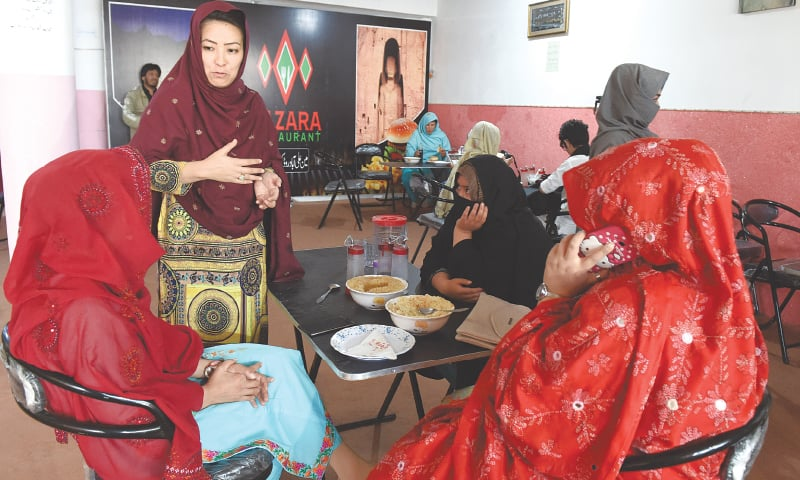 Restaurant owner and women's rights activist Hamida Ali talks to her customers  Photos by Banaras Khan