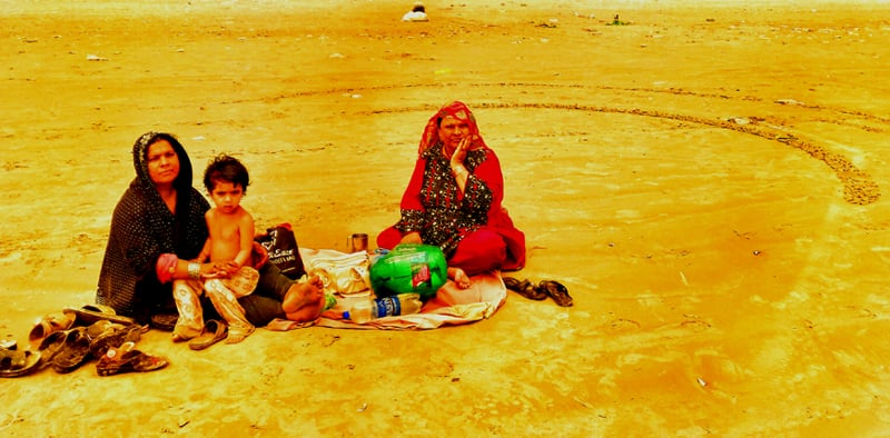 Two women, hailing from Quetta, have a picnic on a deserted part of Seaview beach; their male family members came to the city in search of work opportunities