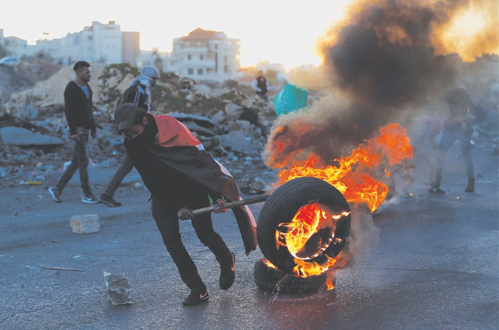 RAMALLAH: A Palestinian demonstrator burns a tyre during clashes with Israeli forces near a security checkpoint on Saturday.—AFP