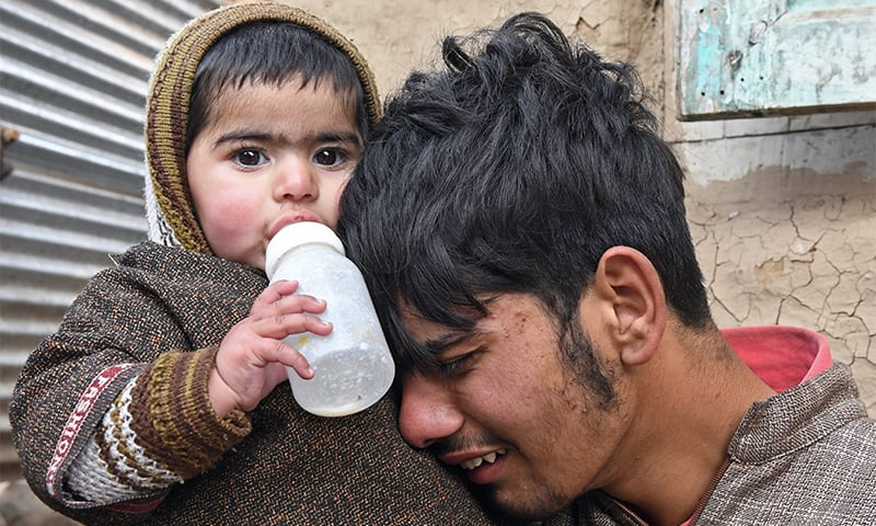 A Kashmiri villager weeps as he holds baby Zaira, who is eleven months old, during the funeral of her mother Ruby Jan in Shopian.— AFP