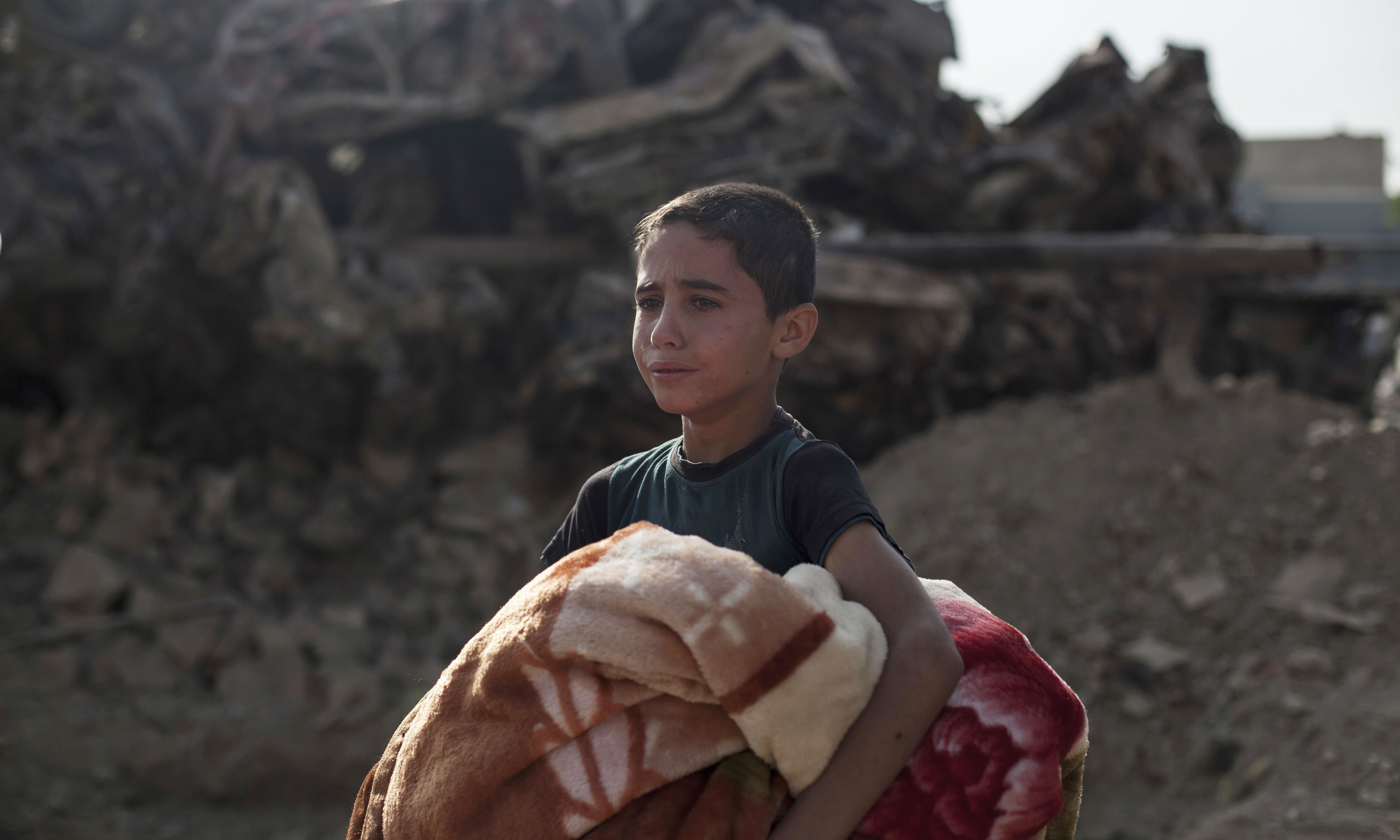 Osama Younes cries as the body of his 15-year-old sister Sana is exhumed for forensic investigation in Mosul.  —AP