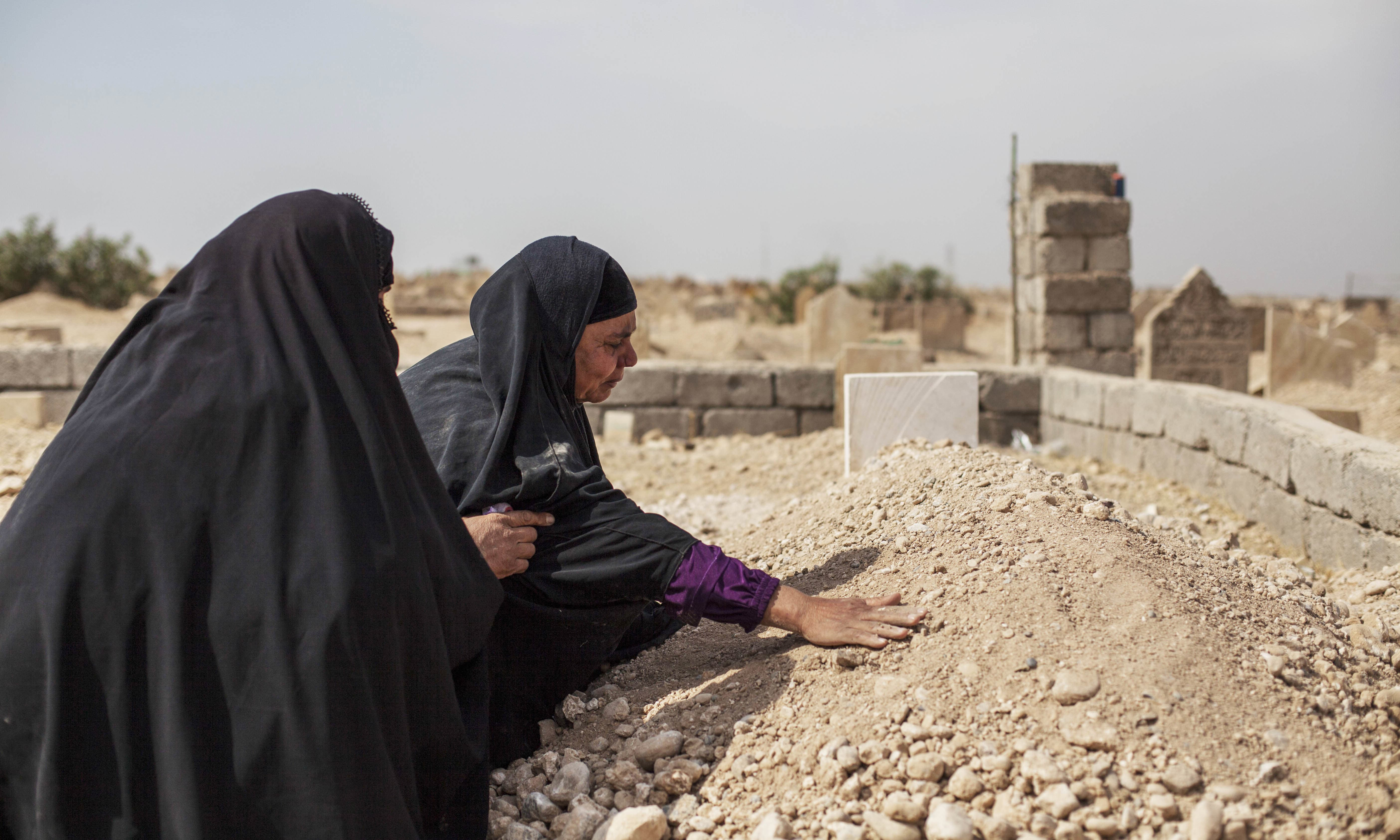 Fatima Ahmed Aswad cries as she touches the grave of her 15-year-old daughter Sana in Mosul. — AP