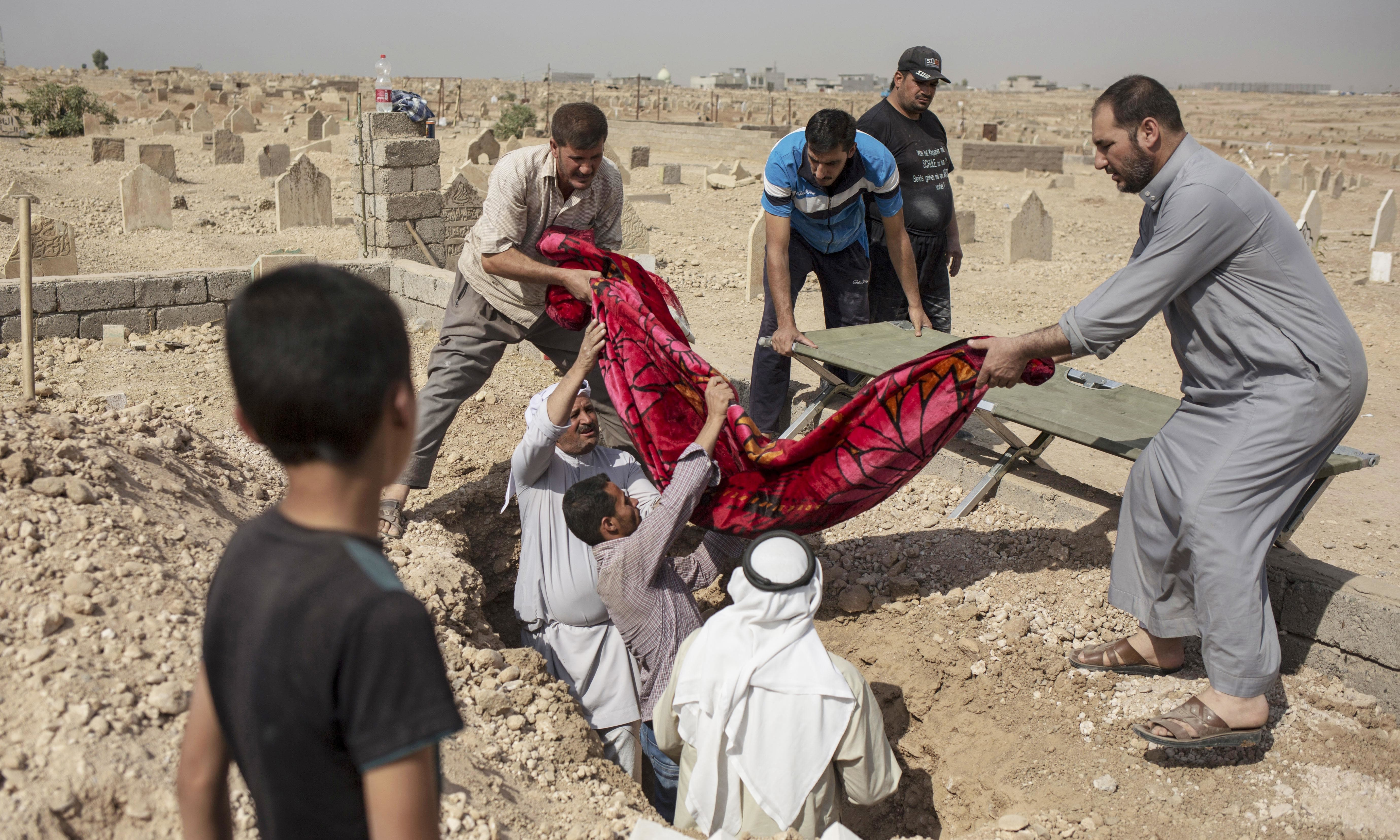 Relatives bury the body of 15-year-old Sana Younes at a graveyard in Mosul. Under Iraqi law, Mosul residents have to exhume the bodies of their relatives in order to receive a death certificate from the government, after which the remains are reburied. —AP