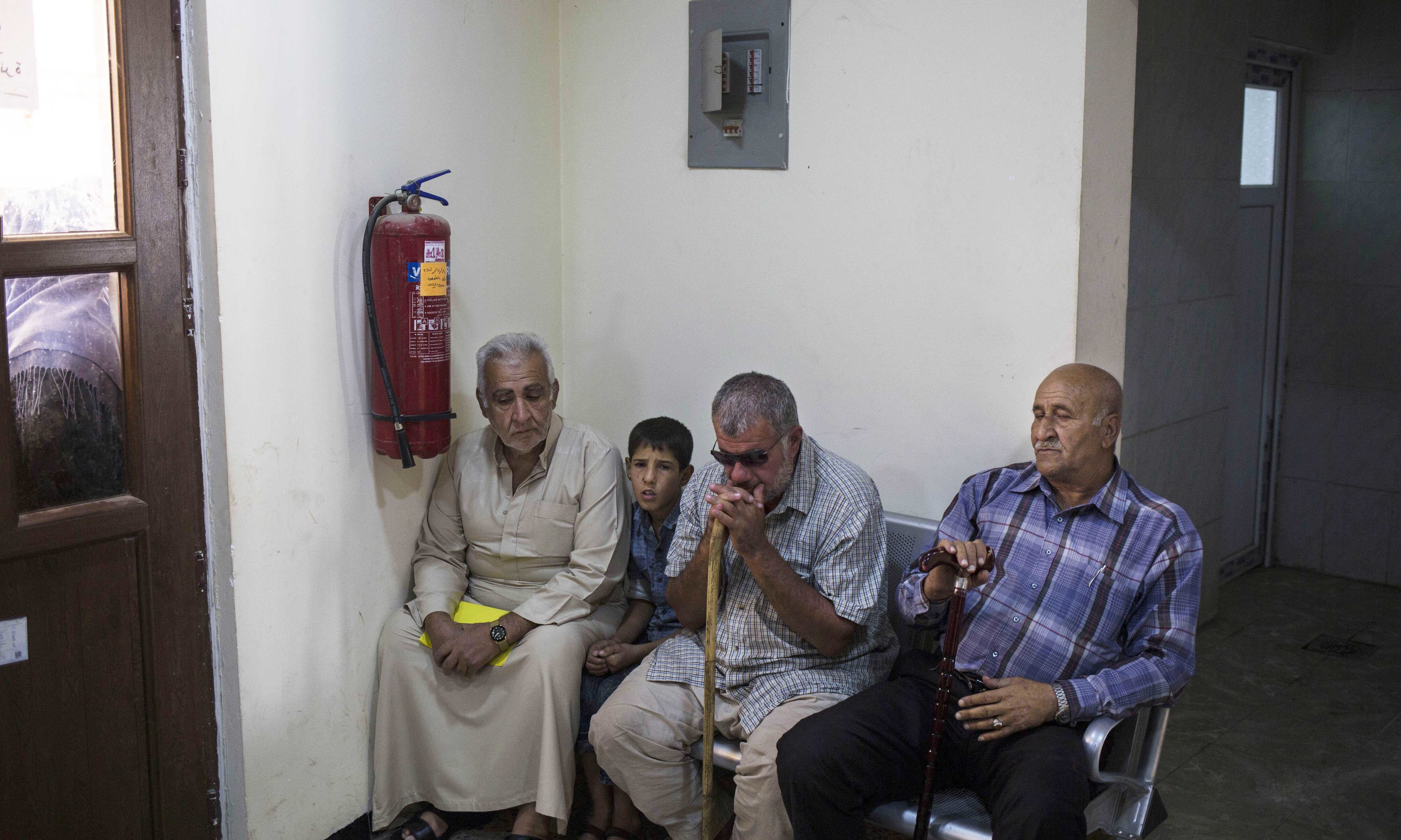 In this Oct. 10, 2017 photo Mosul residents sit inside the waiting room of the morgue in Mosul to pick up death certificates of their relatives. —AP