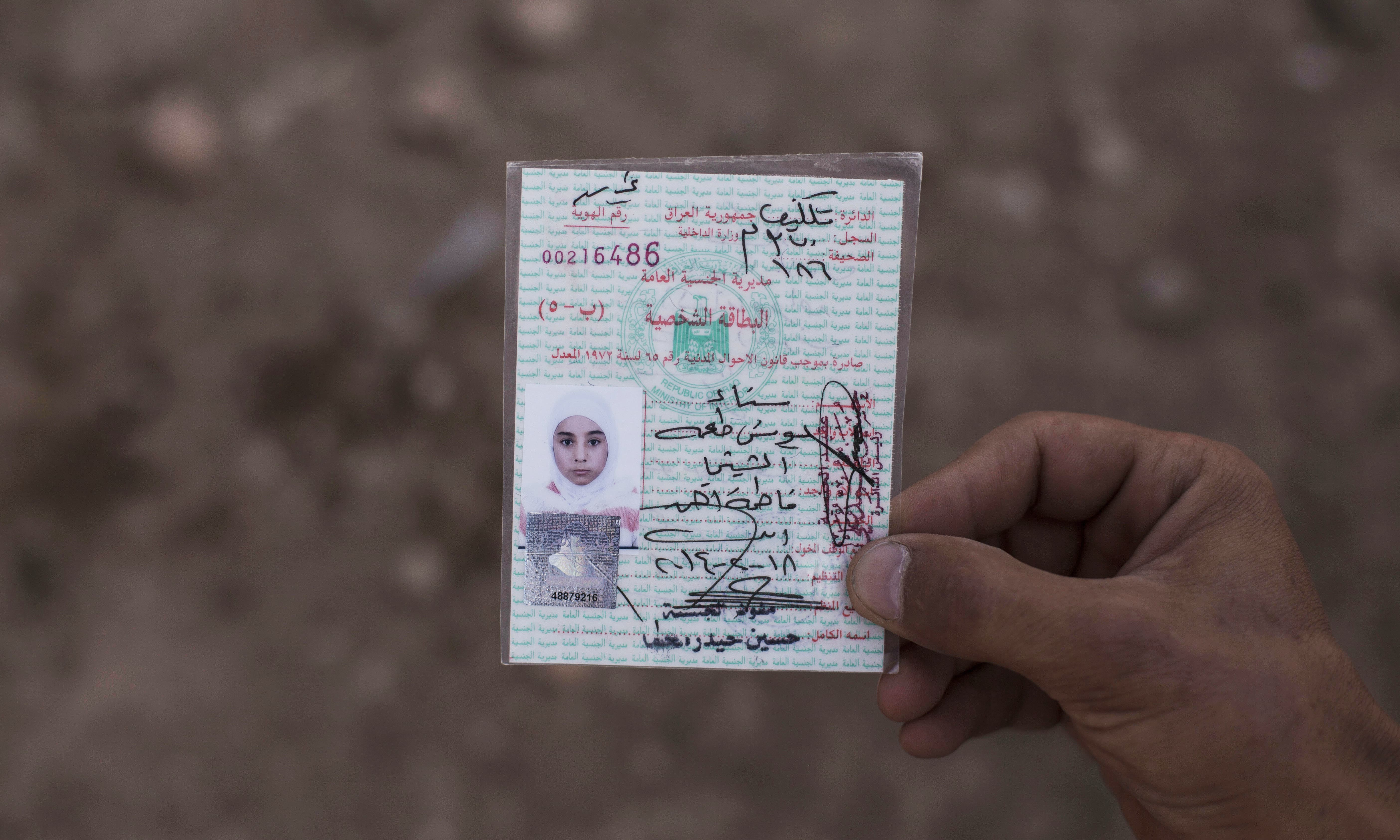15-year-old Sana Younes died in a mortar attack in Mosul during the final battle to drive out Islamic State extremists, and her body was exhumed months later for forensic investigation. In this photo, her brother Salem holds her identification card before her remains are reburied. —AP
