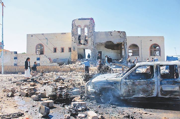 People inspect damage after an air strike by the Saudi-led coalition on a target in Saada, Yemen.— AFP