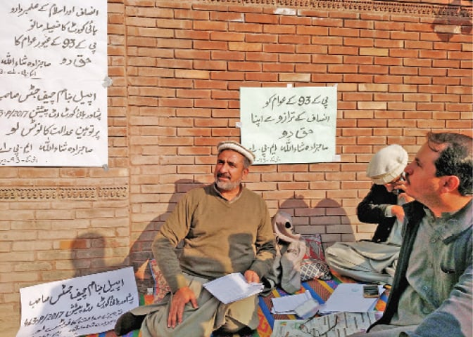 PPP MPA Sahibzada Sanaullah stages a sit-in outside the LG offices in Peshawar on Thursday. — Dawn