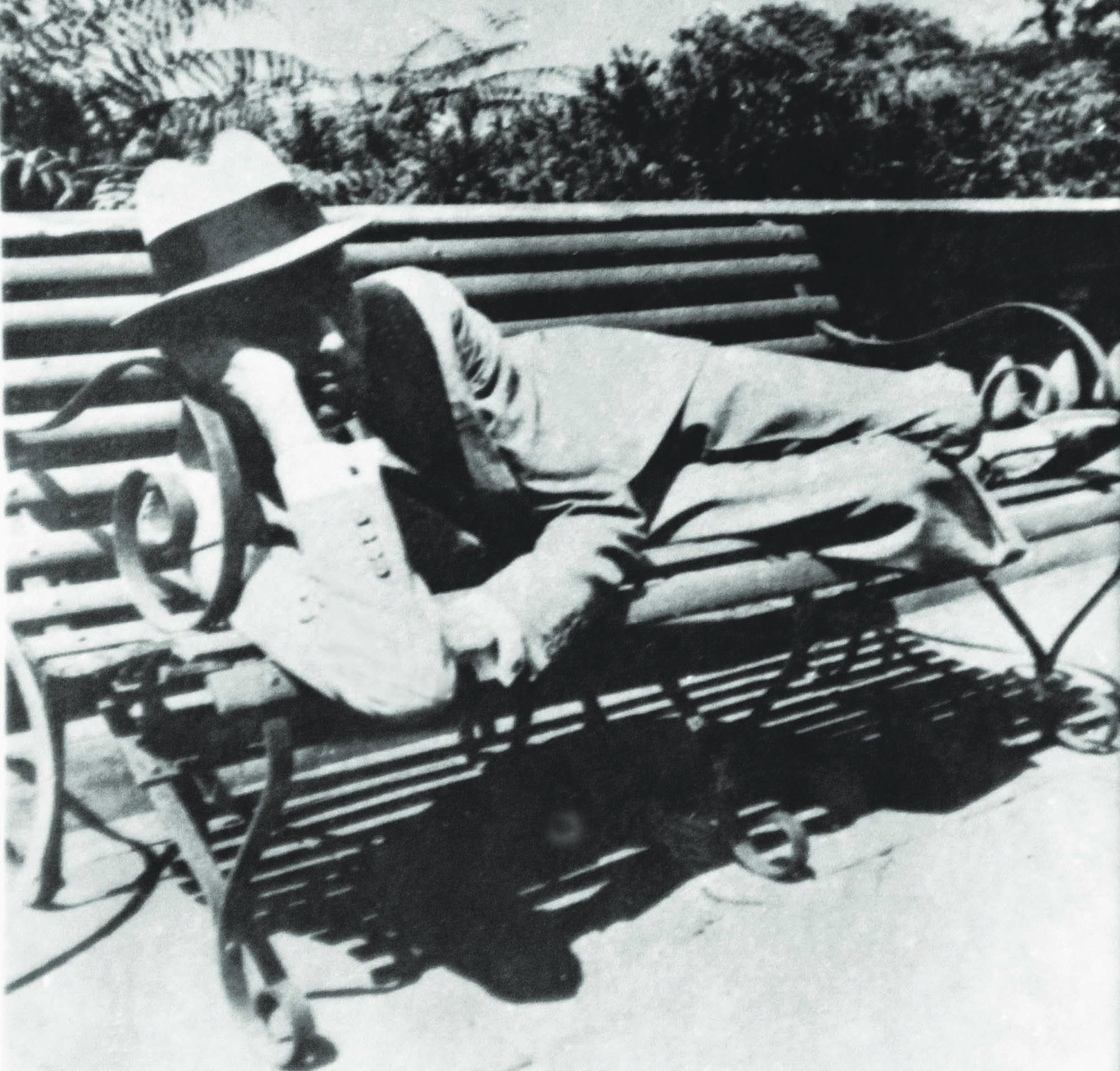 Elegantly dressed in a suit and wearing a hat, Quaid-i-Azam Mohammad Ali Jinnah is seen relaxing on a bench during a visit to Simla. | Photo: PID