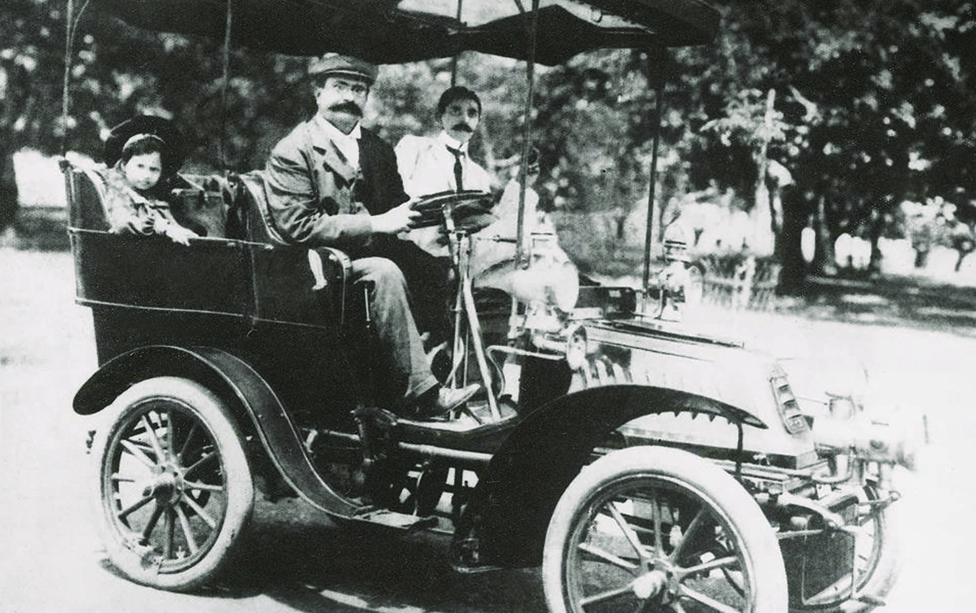 AUTOMOTIVE ELEGANCE: Mr Jinnah seated next to his old-time friend, Pestonjee H. J. Rustomjee, in Bombay in the early 1900s. At the back is Pestonjee's daughter, Homi. Incidentally, Pestonjee H. J. Rustomjee was the maternal uncle of Ardeshir Cowasjee, the esteemed Dawn columnist.