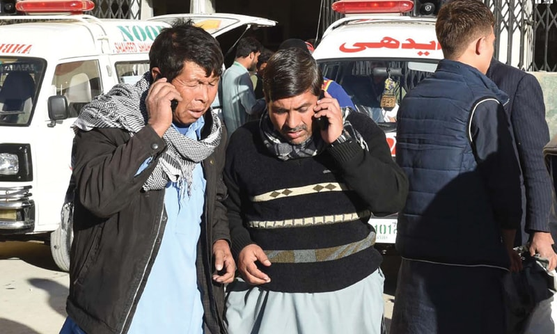 RELATIVES talk on phone outside the hospital on Friday after two members of the Hazara community were killed in an attack.—INP