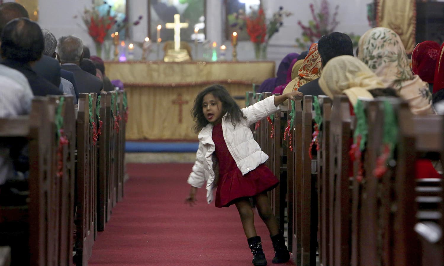 A Christian girl plays beside her mother attending midnight Christmas Mass at Christ church in Karachi  AP
