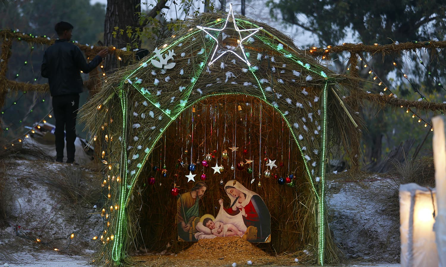 A Christian boy stands beside a Nativity scene set up in an enclosure specially decorated for Christmas celebrations at a Christian neighbourhood of Islamabad  AP