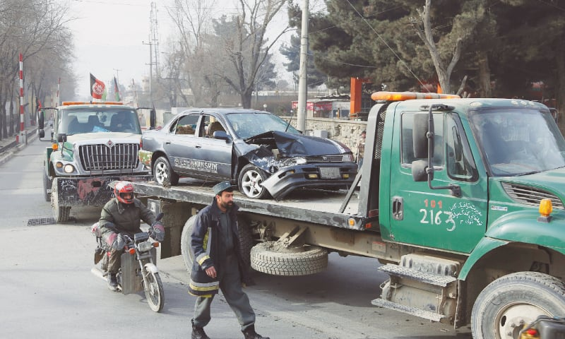 AFGHAN security forces remove a destroyed vehicle after a suicide attack in Kabul on Monday.—AP