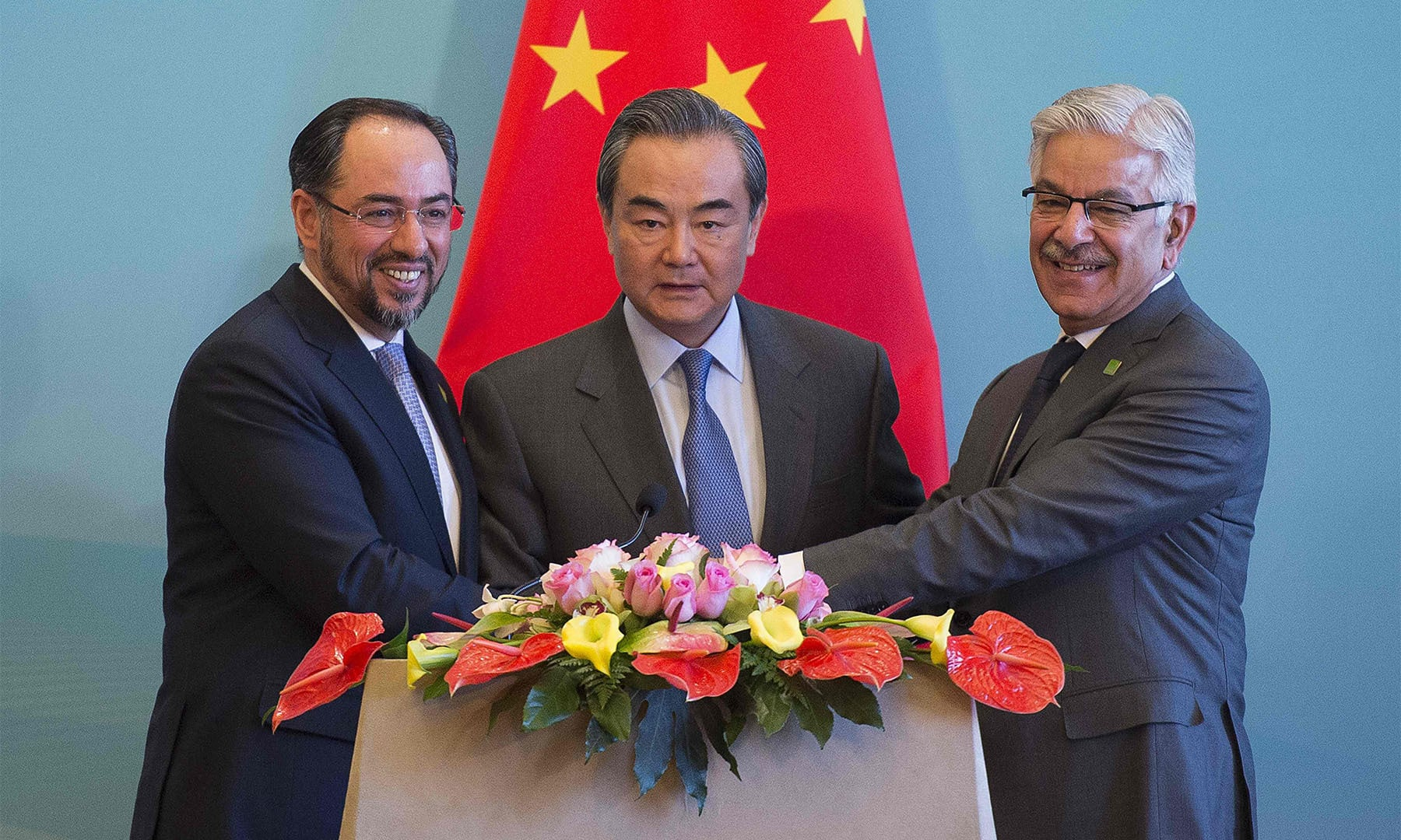 China's Foreign Minister Wang Yi (C), Afghanistan's Foreign Minister Salahuddin Rabbani (L) and Pakistan's Foreign Minister Khawaja Muhammad Asif (R) join hands at the end of a joint press conference after the first China-Afghanistan-Pakistan Foreign Ministers' Dialogue in Beijing on Tuesday.— AFP