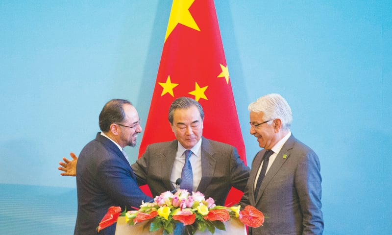 BEIJING: Khawaja Asif on Tuesday shakes hands with Afghan Foreign Minister Salahuddin Rabbani as Chinese Foreign Minister Wang Yi looks on.—AP