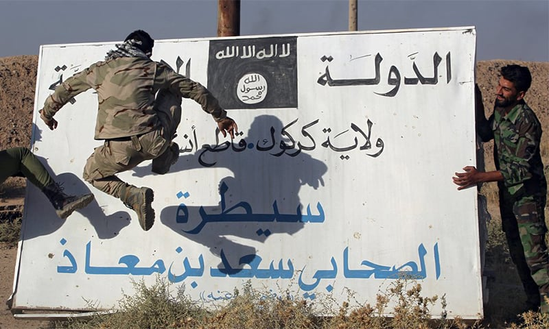 Iraqi fighters kick a billboard bearing the logo of IS in Hawija.— AFP/File