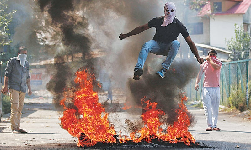 A man in a balaclava jumps over burning debris during a protest in September 2016 in Srinagar against the killings in Indian-administered Kashmir | Danish Ismail / Reuters