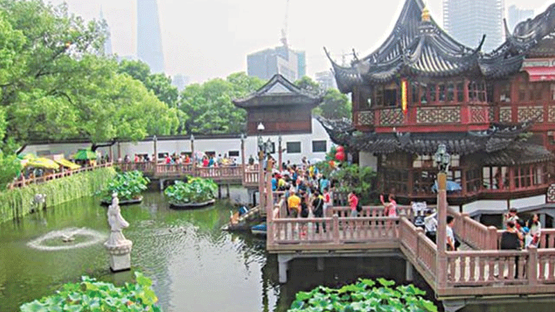 The Yuyaun Garden in the old city against the backdrop of modern structures.