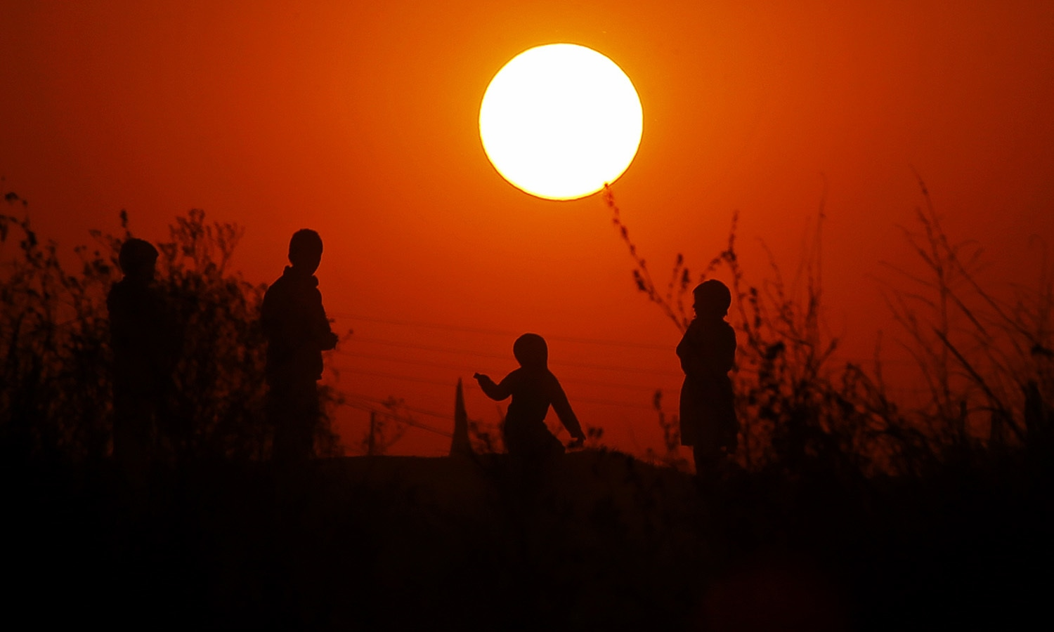 Children from a slum area play as the sun sets for the last time in 2017, on the outskirts of Islamabad, Pakistan, —AP
