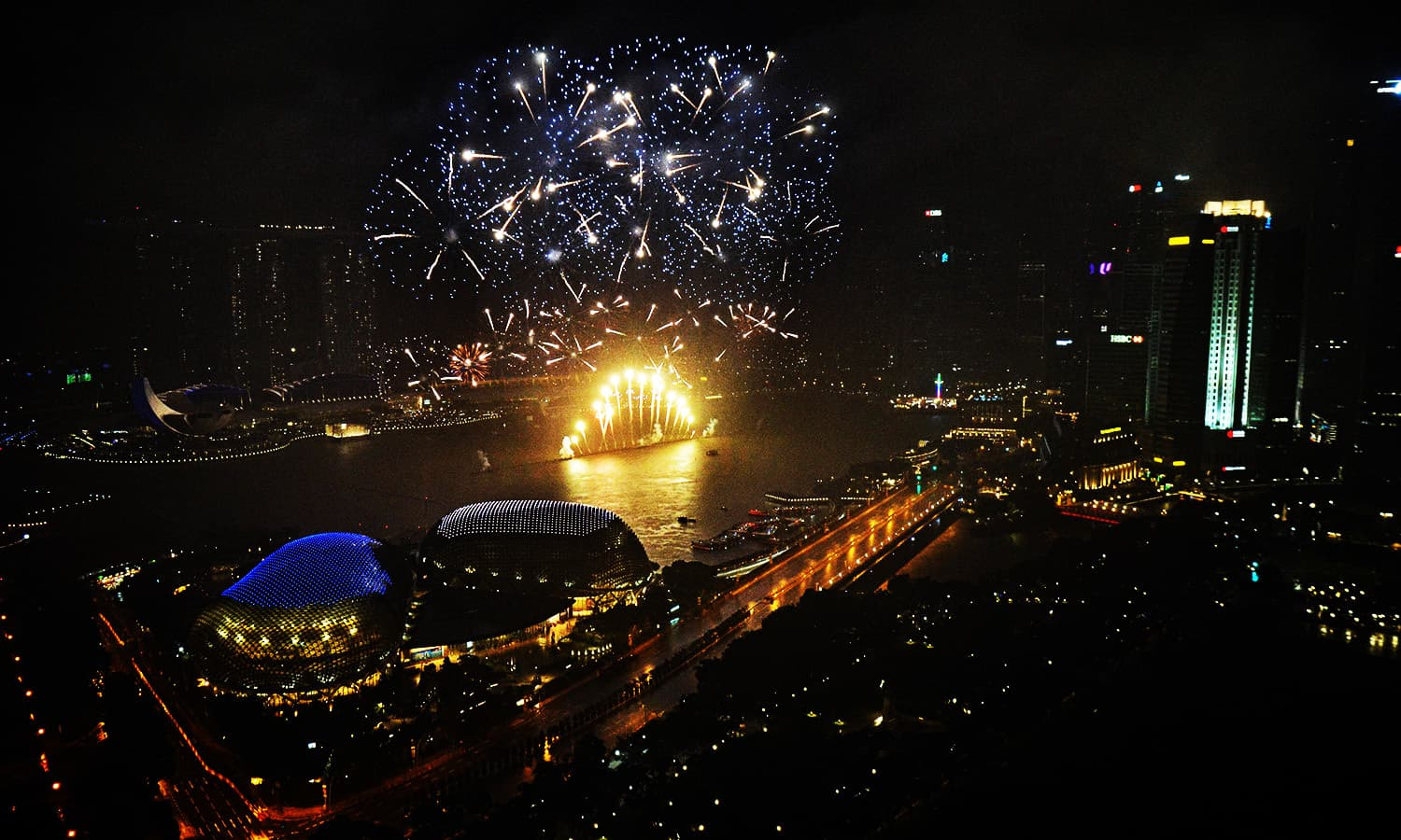 Fireworks illuminate the skyline as the clock strikes midnight during New Year's Eve celebrations in Singapore.—AFP