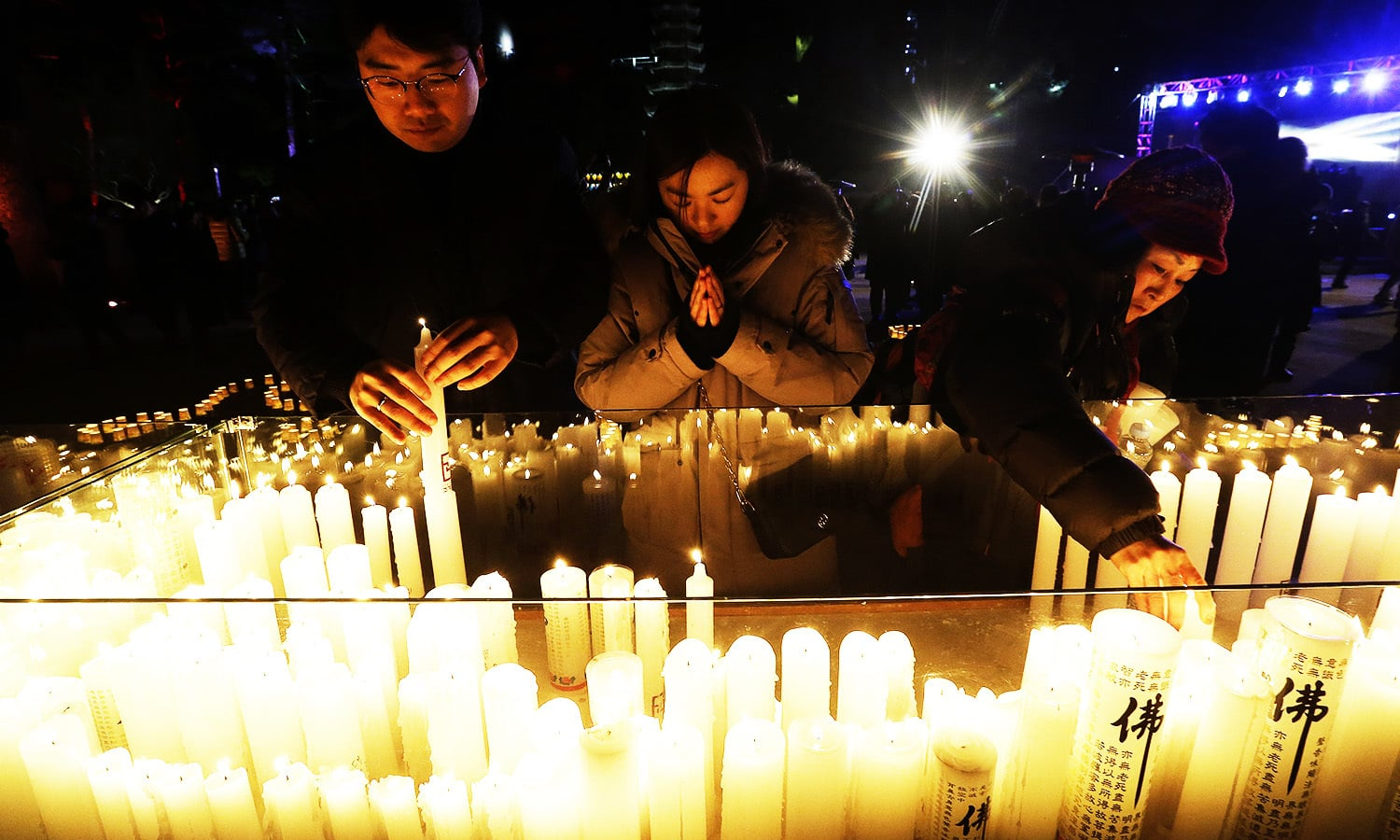 Buddhists place candles during New Year celebrations at Jogyesa Buddhist temple in Seoul, South Korea.—AP