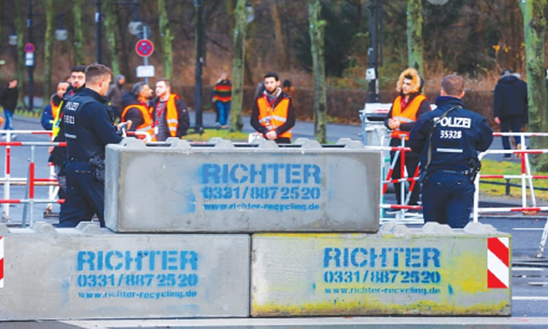 Berlin: Police place concrete barriers near Brandenburg Gate in preparation for the New Year's Eve celebrations.—Reuters