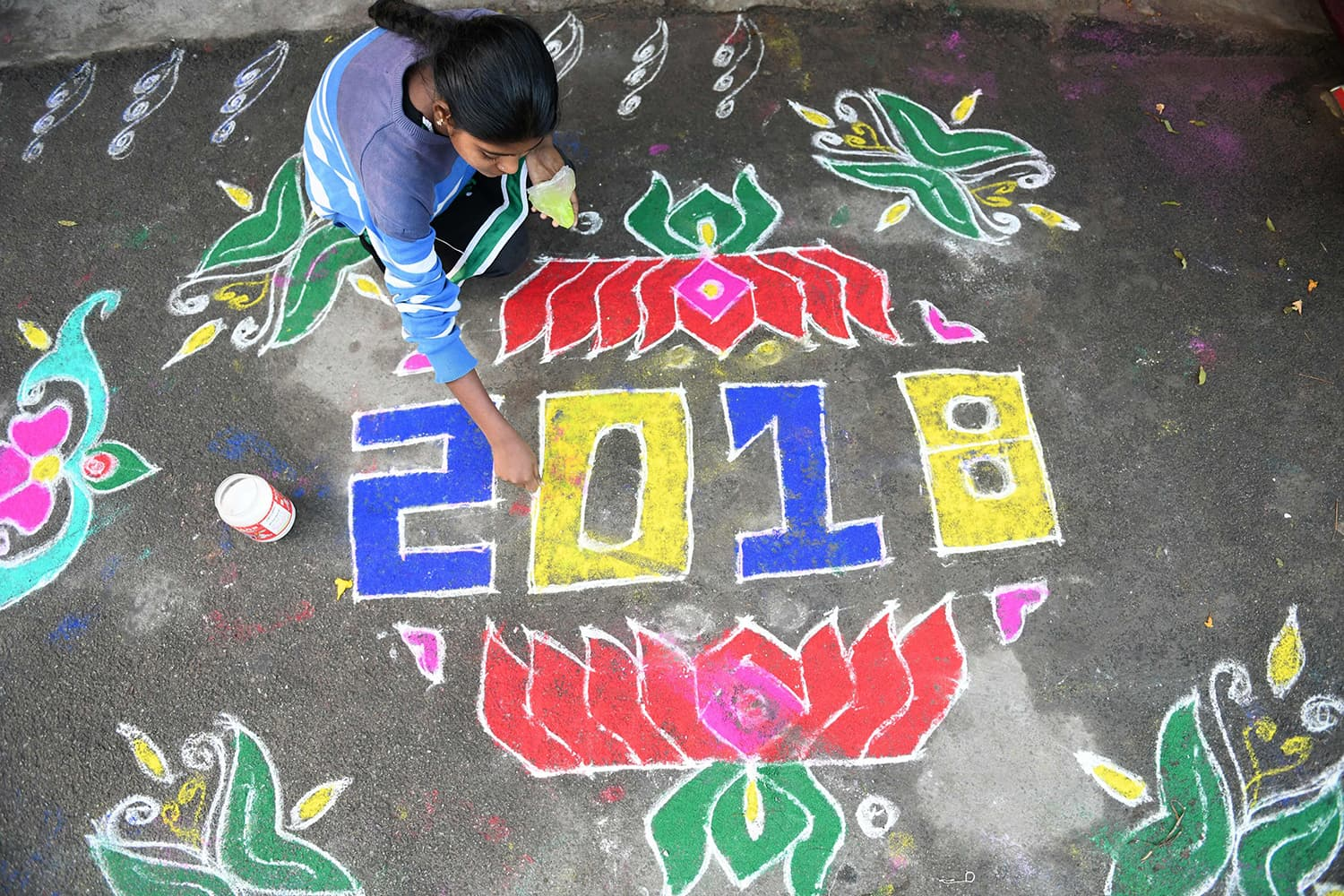 "A woman applies coloured powder to a ""rangoli"", a Hindu ritual design, to usher in the New Year in front of a home in Hyderabad on January 1, 2018. Rangolis are drawn in front of homes early in the morning to welcome relatives and friends to mark the New Year. — AFP"